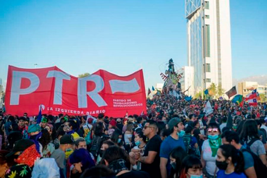 """A crowd of people in Chile, a big red banner says """"PTR."""""""