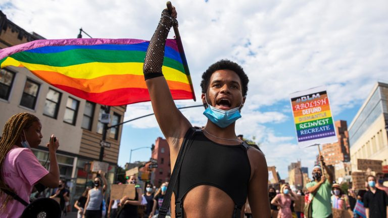 A Black person in a black crop top is holding a rainbow flag. They are in front of a parade.