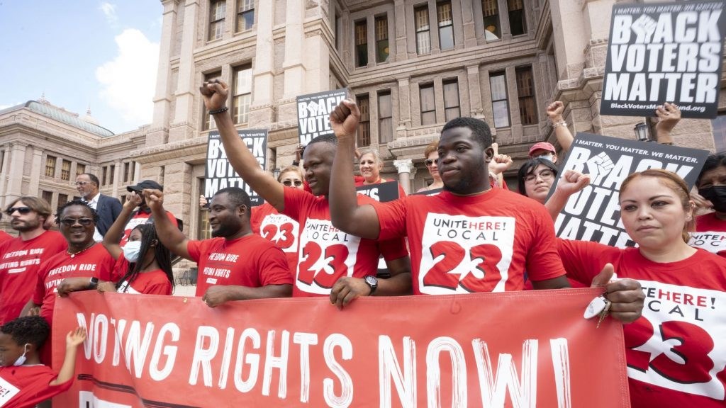 """Members of UniteHere! Local 23, wearing red shirts with their Local's logo, raise their firsts behind a sign that reads """"Voting Rights Now!"""""""