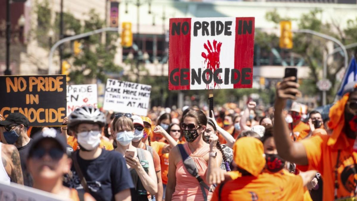 """Protesters marching on Canada Day. A sign has the Canadian colors and says """"No Pride in Genocide."""""""