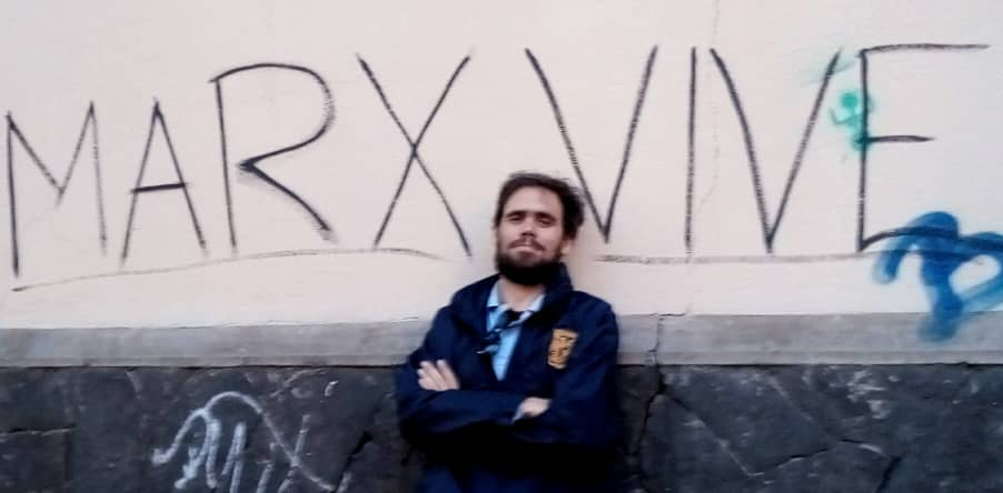 """Cuban Marxist Frank García Hernández stands with his arms crossed against a wall that reads """"Marx Vive"""" (Marx Lives)"""