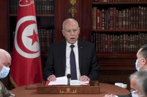 Tunisian President Kais Saied sits at a conference table wearing a suit. The Tunisian flag and a wall of books are in the background.