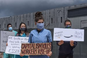 Four healthcare workers, including co-author of this article Mike Pappas, stand in scrubs and masks in front of an Amazon warehouse holding signs in support of better wages and safer working conditions for Amazon workers.
