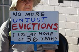 """An older woman wearing a hat holds a sign that reads """"No More Unjust Revictions: I Lost My Home of 36 Years"""""""
